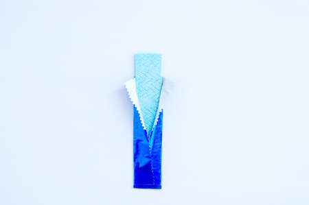 Close-up of chewing gum unwrapped in a blue package. White background.
