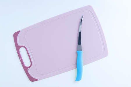Kitchen pink cutting plastic board and knife on a white table.