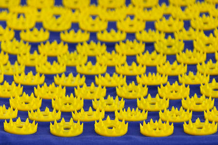 Blue massage mat with yellow plastic needles. Selective focusing. 스톡 콘텐츠