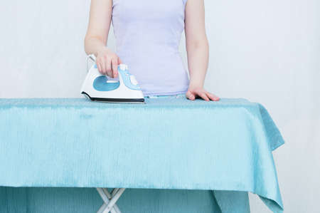 Caucasian woman ironing curtains while standing by the ironing board.