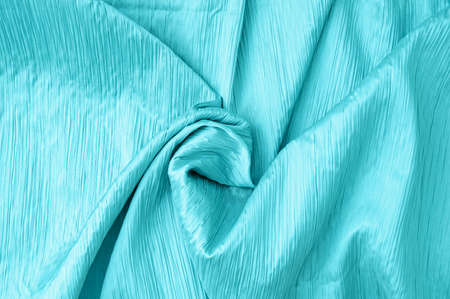 close-up of a pleated turquoise curled fabric. Curtains and textiles.