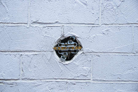 Electrical outlet wires in a gray brick wall. Home improvement.