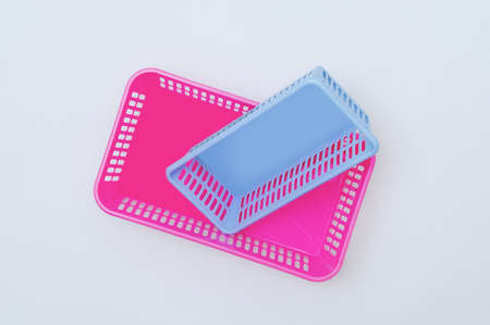 Two plastic boxes for home pink blue on a white background. View from above.