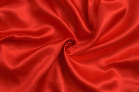 Background of twisted red satin fabric with folds.