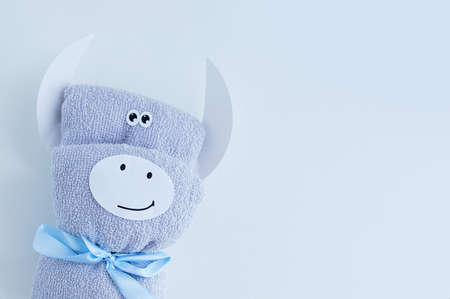 Gray terry towel folded in the form of a white bull on a white background. 스톡 콘텐츠