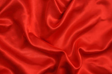 Background of red satin fabric with folds. Curtains and textiles.