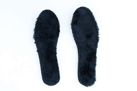 Black fur insoles for winter shoes on a white background.