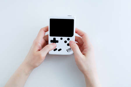 White game console with black display in the hands of a Caucasian woman. White background. 스톡 콘텐츠