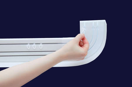 A Caucasian woman hand puts plastic hooks on a white curtain rod. Dark blue background.