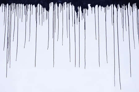 Black smudges of paint on top of a white wall. Gloomy background.