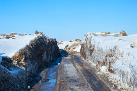 Winter landscape. The road between the melting snowdrifts in the afternoon.