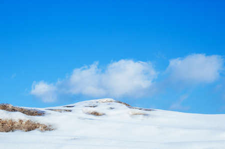 Winter outdoors landscape in the mountains against the blue sky.