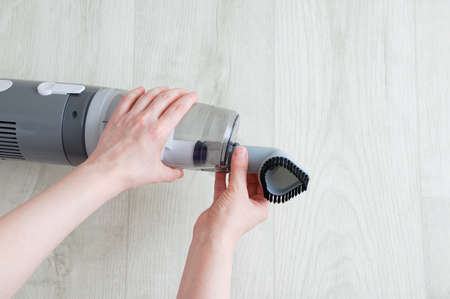 The hand of a caucasian woman puts on a small nozzle on a gray vacuum cleaner on a white wooden background. Stock Photo