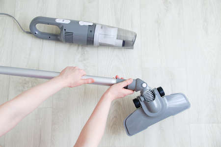 The hand of a Caucasian woman puts a brush attachment on a gray vacuum cleaner on a white wooden background. 스톡 콘텐츠