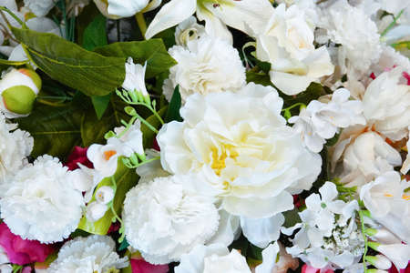 Bouquet of white artificial flowers of rose, carnation and peony close-up. 스톡 콘텐츠