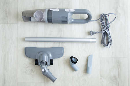 Manual gray vacuum cleaner. Disassembled set of vacuum cleaner nozzle brush on white wooden background.