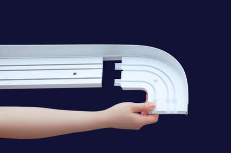 Caucasian woman hand collects white plastic curtain rod. Dark blue background.