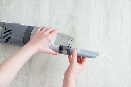 Caucasian woman's hand putting on small crevice tool on gray vacuum cleaner on white wooden background.