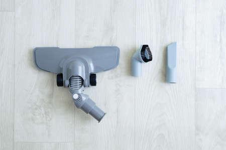 Disassembled vacuum cleaner brush set on white wooden background.