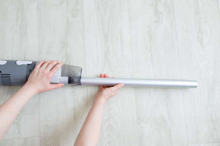 Caucasian woman hand puts metal tube on gray vacuum cleaner on white wooden background.