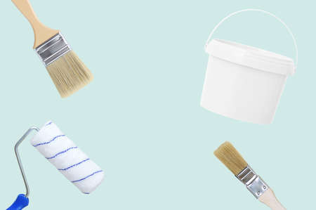 Wall painting set. Paint bucket, paint roller and brushes. Blue background.
