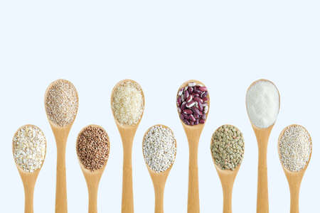 Cereals in a wooden spoon in a row on a white background close-up. 스톡 콘텐츠