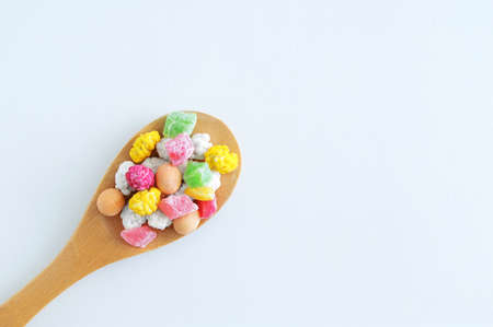 Multicolored sweets and dry fruit slices on a wooden spoon. White background. 스톡 콘텐츠