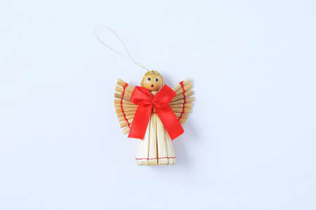 Christmas decoration straw angel with a red bow on a white background.