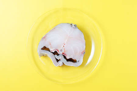 Raw cod fish steak on a transparent glass plate. Yellow background.