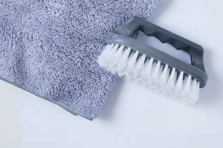 Gray household brush with stiff bristles and a rag for cleaning on a white background. 스톡 콘텐츠