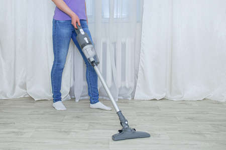 Handheld gray vacuum cleaner in the hand of a caucasian woman. Vacuum the floor in the room.