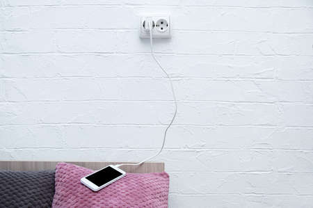 White smartphone lying on the pillow of the bed connected to a charging electrical outlet.