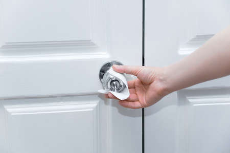 Caucasian woman hand holds doorknob through white antibacterial napkin.