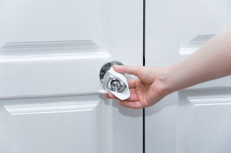 Caucasian woman hand holds doorknob through white antibacterial napkin.