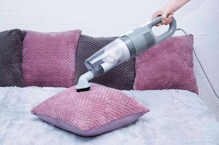 Handheld gray vacuum cleaner in the hand of a caucasian woman. Vacuuming the pillow on the bed. Фото со стока