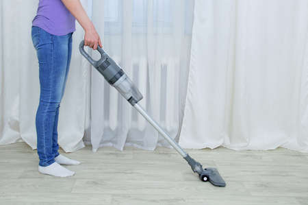 Handheld gray vacuum cleaner in the hand of a standing caucasian woman. Vacuum the floor in the room.
