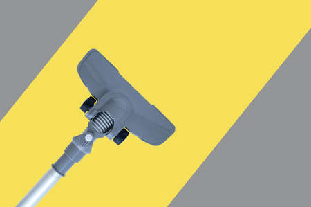 Gray vacuum cleaner with a floor nozzle on a yellow-gray striped background.