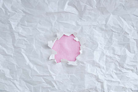 Texture of white crumpled paper with a torn hole in the middle. 스톡 콘텐츠 - 165543522