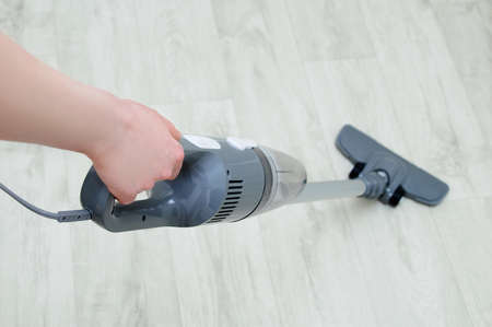 Handheld gray vacuum cleaner in the hand of a Caucasian woman. Vacuum the floor. View from above. Фото со стока
