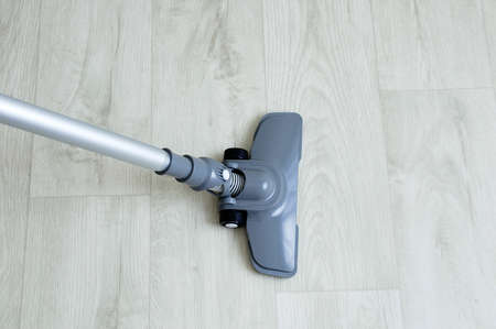 A gray vacuum cleaner with a floor nozzle on wooden carpet background.