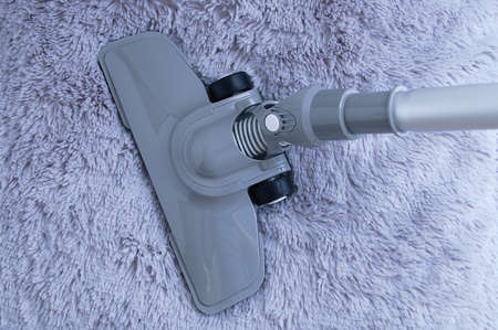 Gray vacuum cleaner with a floor nozzle against the background of a blue fur carpet. 스톡 콘텐츠