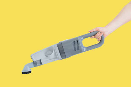 Handheld gray vacuum cleaner in the hand of a Caucasian woman on a yellow background. 스톡 콘텐츠