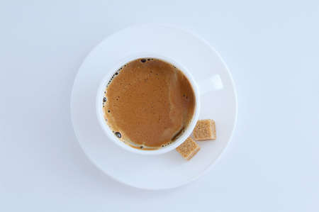 White cup of coffee with froth and cane sugar cubes on a saucer on a white background.