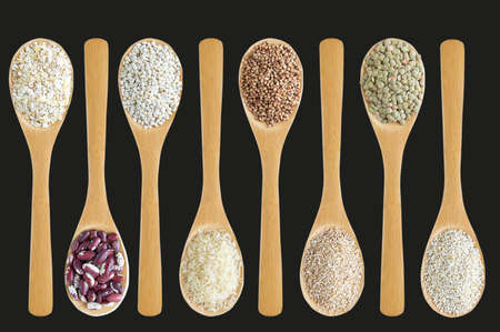 Cereals in a wooden spoon in a row on a graphite background close-up.
