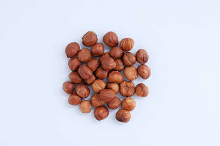 A handful of a heap of peeled hazelnuts on a white background. Фото со стока