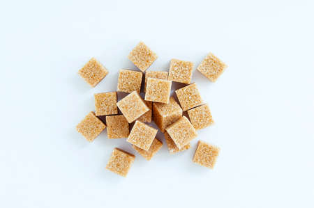 Cane sugar cubes heap close-up on a white background.