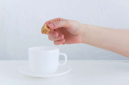 The hand of a Caucasian woman puts a piece of cane sugar into a white cup.