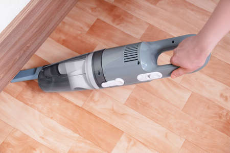 Handheld gray vacuum cleaner in the hand of a caucasian woman. Vacuum the floor under the bed.