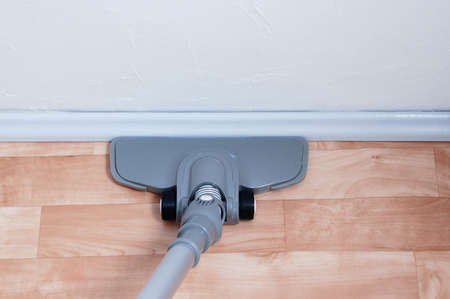 A gray vacuum cleaner with a nozzle on a beige floor near the baseboard.