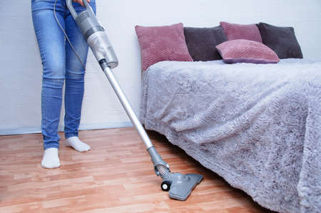 Handheld gray vacuum cleaner in the hand of a Caucasian woman in jeans. Vacuum the floor in the room. 스톡 콘텐츠